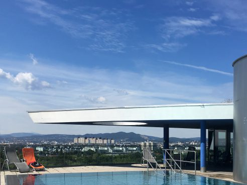 Pool on the roof of a high-rise building with 2 sun loungers