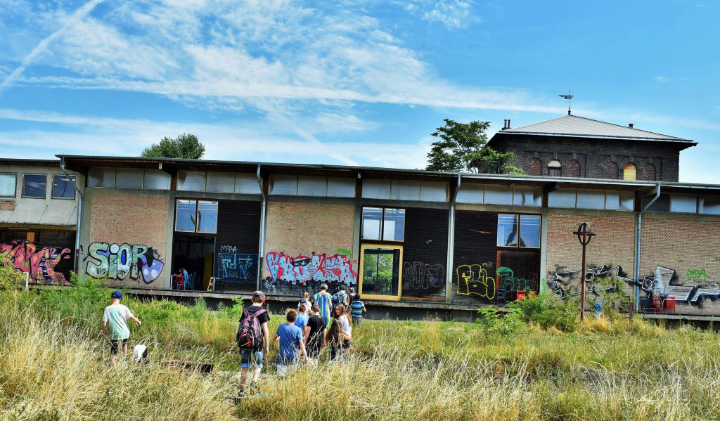 a group of people in front of a building with graffiti