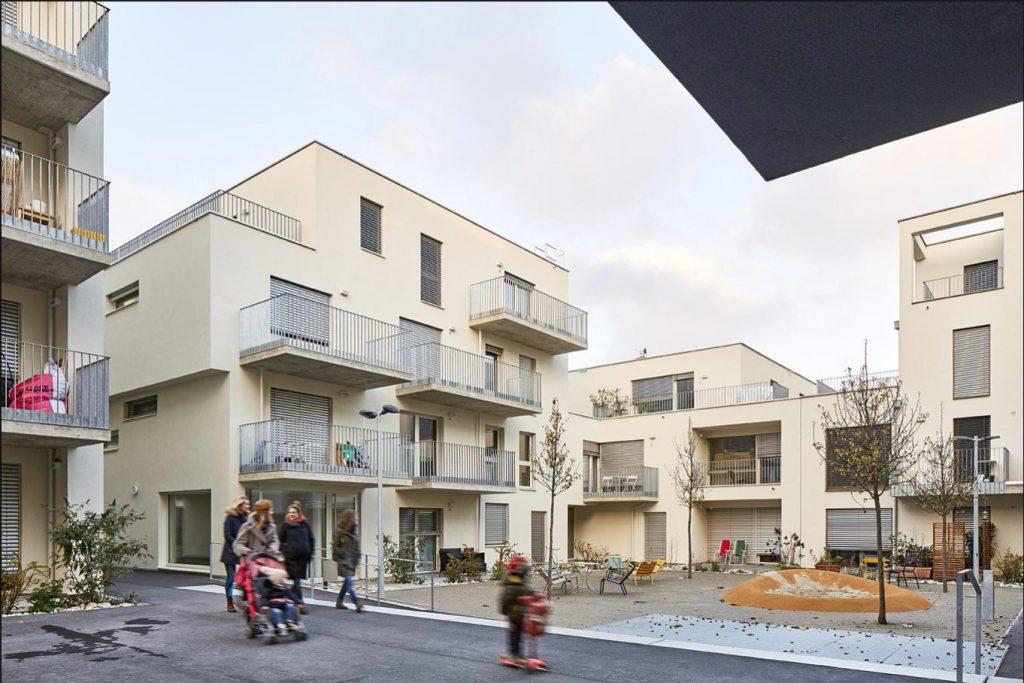 Wohnhäuser in beige mit Balkonen und kleinem Innenhof-Spielplatz