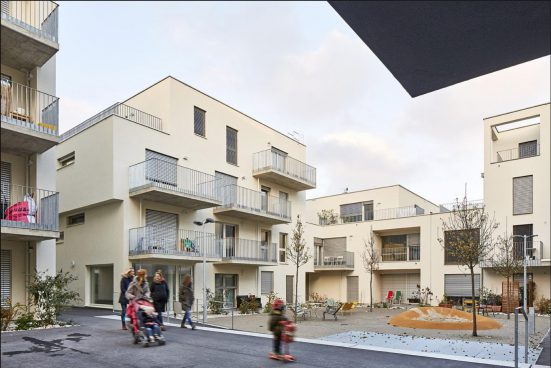 Residential houses in beige with balconies and small inner courtyard playground