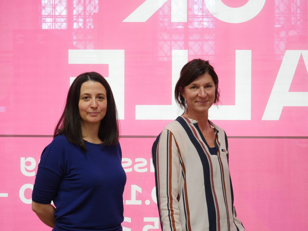 Two women against a pink background