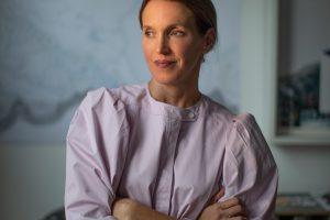 Frau blickt zur Seite mit blassrosa Bluse
