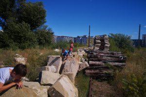 Kinder auf großen Steinen auf einer Brachfläche neben Wohnhäusern