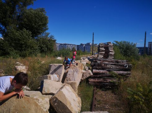 Children on large stones in a wasteland next to residential buildings