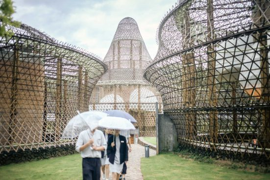 People with white umbrellas walk between bamboo buildings