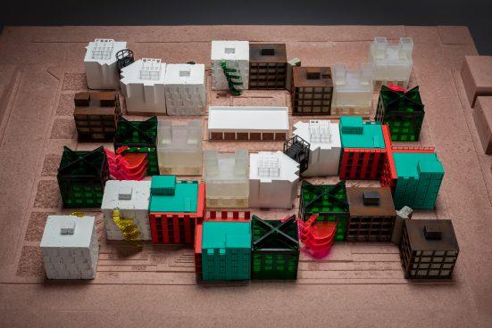 Architekturmodell mit grünen, weißen, brauen und transparenten Häusern