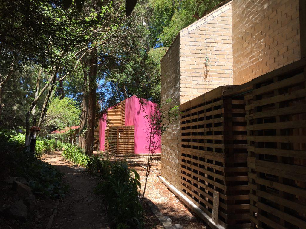 Häuser aus Ziegel und Holz mit pink gefärbten Wänden