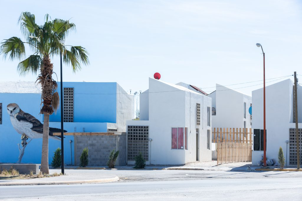 Houses in white and blue, on one house a large bird is painted, in front of it is a palm tree