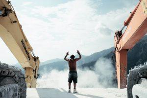 Mann mit erhobenen Armen zwischen 2 großen Baggern