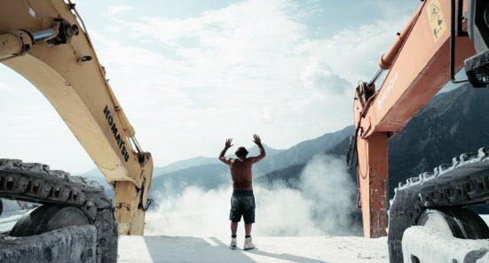 Man with raised arms between 2 large excavators