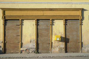Fassade mit geschlossenem Geschäftsportal und schiefem Briefkasten