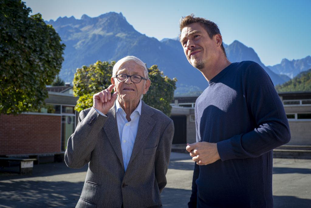 an old man with glasses and a young man stand in the sunshine in front of a mountain backdrop