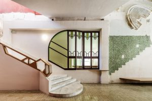 Interior with stone staircase and green and pink wall painting