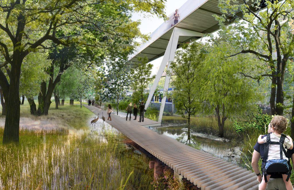 Fußgängerbrücke über eine Teich die durch einen Wald führt, im Vordergrund ein Mann mit Kind am Rücken