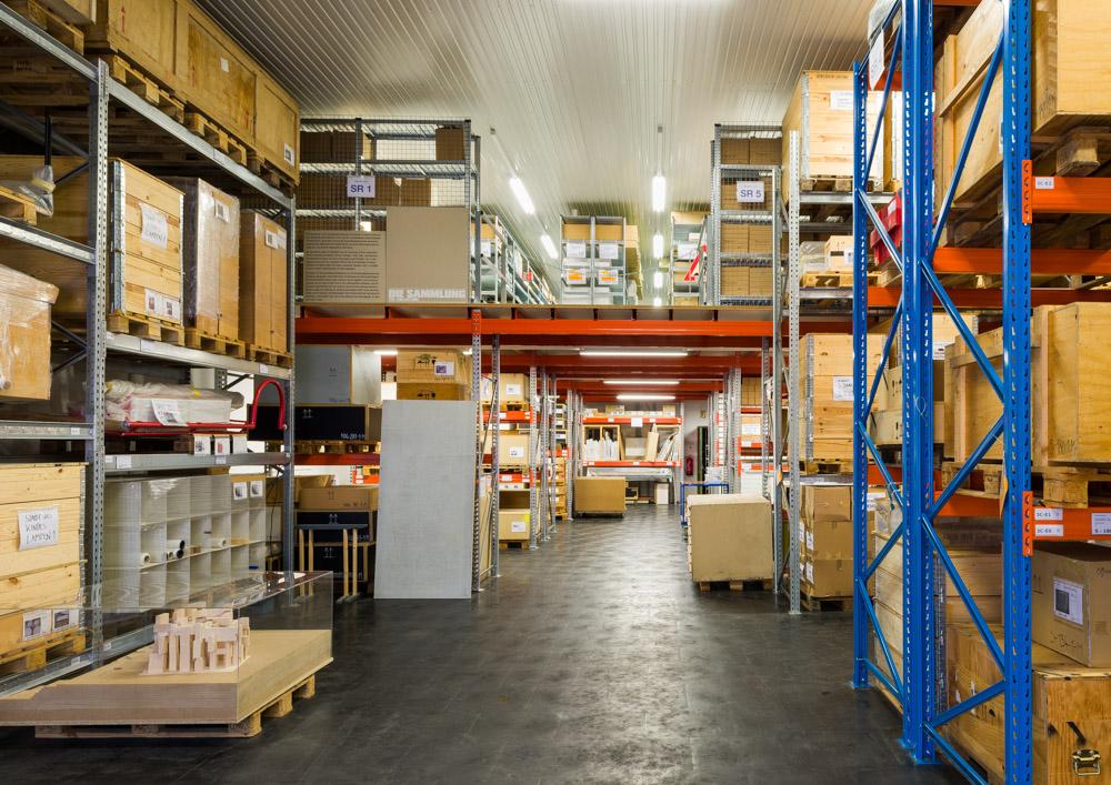 Halle mit vielen Regalen, darin viele Karton- und Holzkisten