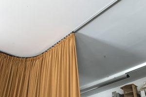 Ein brauner Vorhang auf einer gebogenen Vorhangschiene