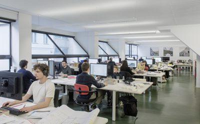 Büroraum mit großen schrägen Fenstern und vielen Mitarbeitern
