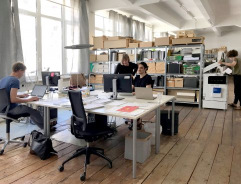 Büroraum mit 4 Menschen und Regal mit vielen Schachteln